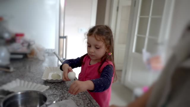 little cute girl preparing egg for breakfast in the kitchen. lovely kid making breakfast for herself - one girl only stock videos & royalty-free footage