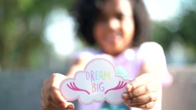 Kleine niedliche Mädchen zeigen Aufsatz: Große Träume