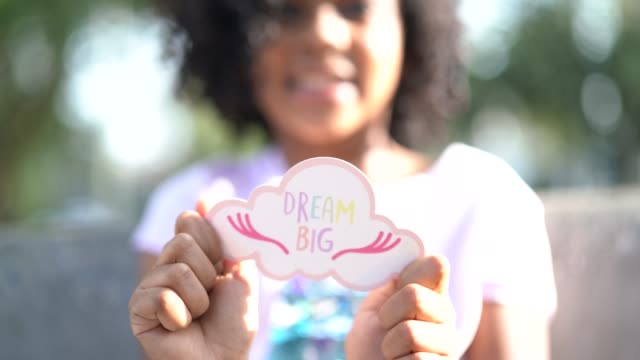 little cute girl showing paper: dream big - hope concept stock videos and b-roll footage