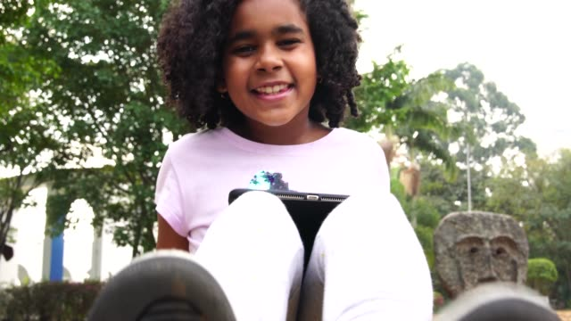 little cute girl using tablet at park - pardo brazilian stock videos & royalty-free footage