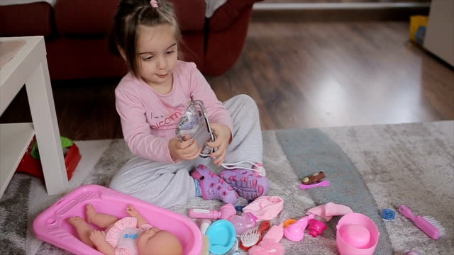 vídeos de stock e filmes b-roll de little doctor,girl playing with doll at home - boneca