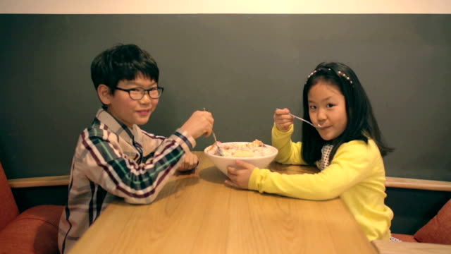 little east asian boy and girl enjoying desert in a cafe - east asian ethnicity video stock e b–roll