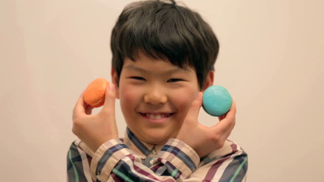 Little East Asian boy playing with macaroon