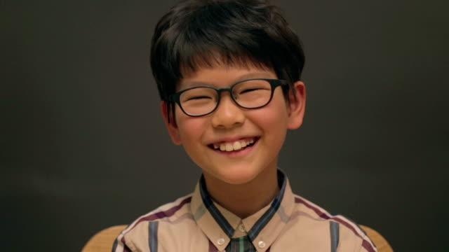 little east asian boy wearing glasses laughing - east asian ethnicity video stock e b–roll