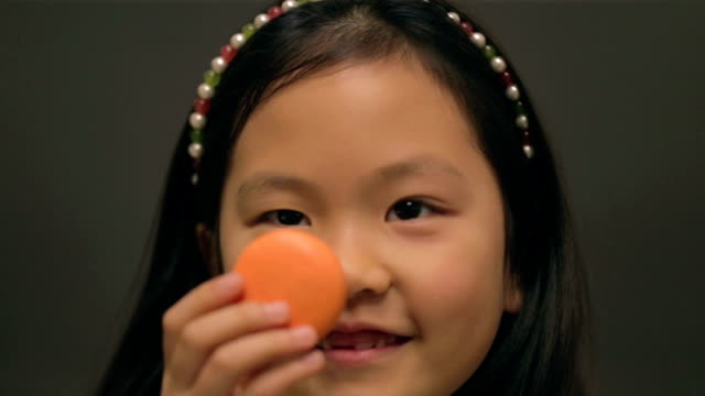 little east asian girl playing with macaroon - macaroon stock videos and b-roll footage