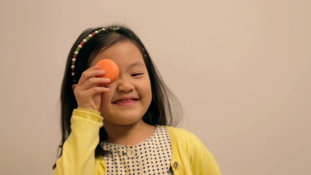 little east asian girl playing with macaroon - macaroon stock videos & royalty-free footage