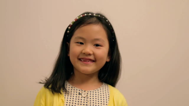Little East Asian girl wearing hairband smiling