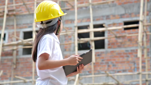 little engineer with tablet computer in construction site - work helmet stock videos & royalty-free footage