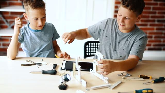 vídeos de stock e filmes b-roll de little engineers! elementary-age children collaborate on 'robot' creation. - nerd