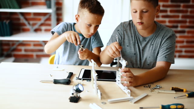 vídeos de stock e filmes b-roll de little engineers! elementary-age children collaborate on 'robot' creation. - engenheiro