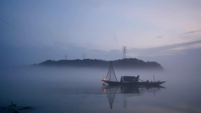 kleine vissersboot op rustige meerwater in mistige dag