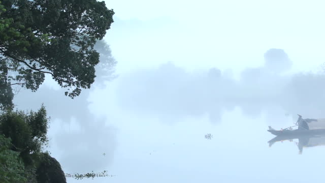 little fishing boat on tranquil lake water in foggy day