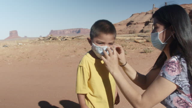 little four or five years old navajo boy in monument valley arizona tribal park  being assisted in putting on his covid-19 corona virus facemask - indigenous north american culture stock videos & royalty-free footage