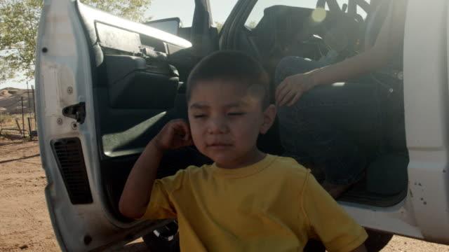 vídeos de stock, filmes e b-roll de menino navajo de quatro ou cinco anos de idade em monument valley arizona tribal park sendo assistido em colocar em seu covid-19 corona virus facemask - tribo norte americana