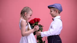 Little gentleman boy presenting bouquet of roses to young lady, Valentines day