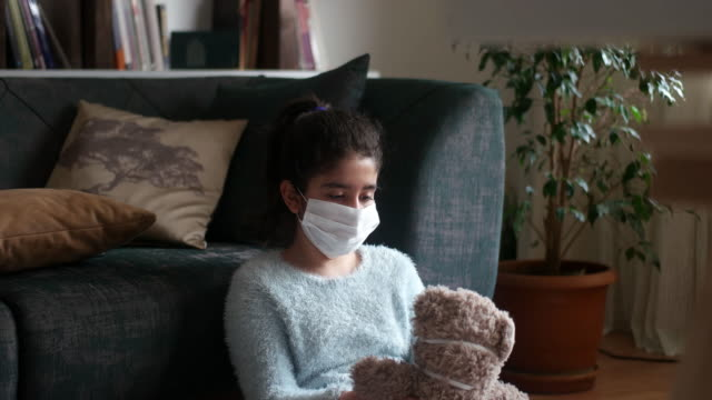 little girl and big plush bear in medical masks. - support stock videos & royalty-free footage