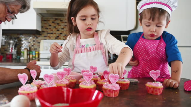 little girl and boy cooking valentine muffins with grandmother - valentine's day stock videos & royalty-free footage