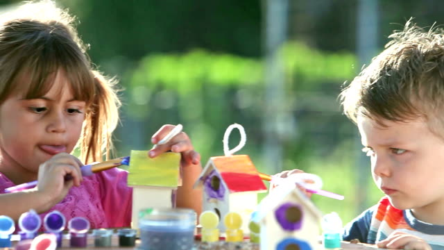 little girl and boy painting birdhouses - art class stock videos & royalty-free footage