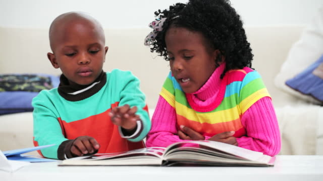 Little girl and boy reading a book