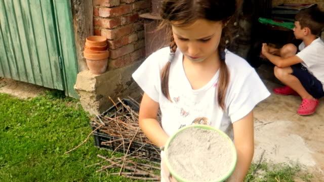 stockvideo's en b-roll-footage met klein meisje en jongen, broers en zussen spelen met ash, vuil, modder met emmer in arme landhuis - arm lichaamsdeel