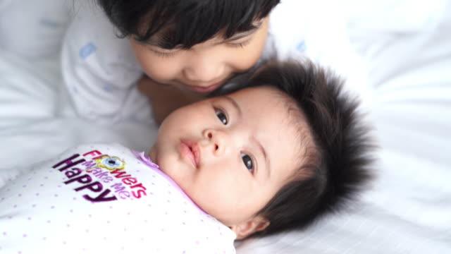 小さな女の子と彼女の赤ちゃんの妹のベッドの上 - 生後2ヶ月から5ヶ月点の映像素材/bロール