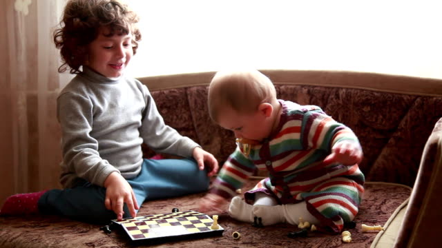 little girl and her baby sister playing with chess pieces - babies in a row stock videos & royalty-free footage