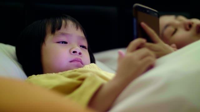 vídeos y material grabado en eventos de stock de niña y su madre usando el teléfono en la noche - nativo digital