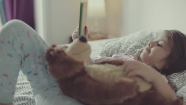 little girl and her teddy bear watching tablet - teddy bear stock videos and b-roll footage