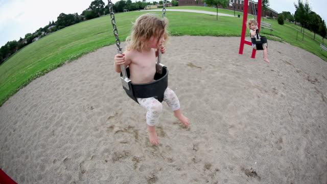 MS Little girl and little boy on swing then mother pushes them higher / Toronto, Ontario, Canada