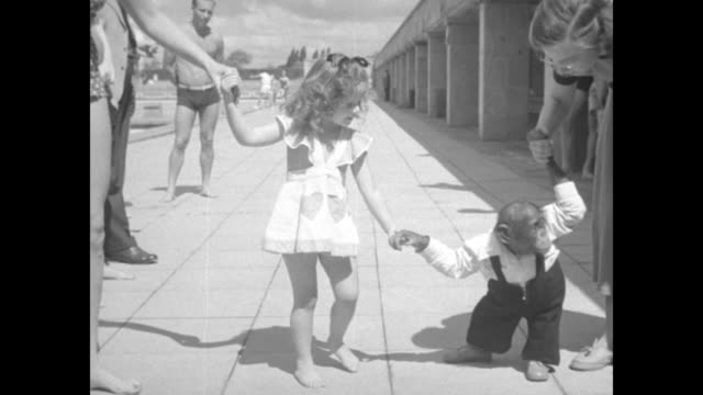 little girl and man holding hands of chimpanzee people watching / same girl and woman holding hands of chimp chimp lets go of girl's hand / girl... - 1951 stock-videos und b-roll-filmmaterial