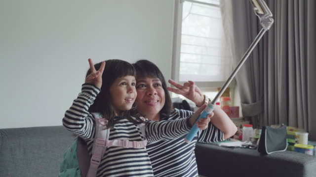 小さな女の子とママのリビング ルームで電話で、selfie を取って笑顔します。 - 撮影テーマ点の映像素材/bロール