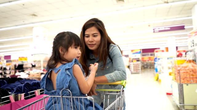 little girl and mother having fun shopping together in supermarket  , slow motion - study stock videos & royalty-free footage