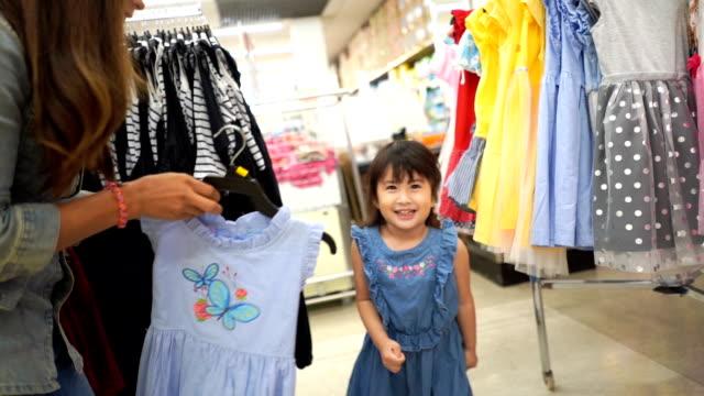 vídeos de stock e filmes b-roll de little girl and mother having fun shopping together in supermarket  , slow motion - viciado em compras
