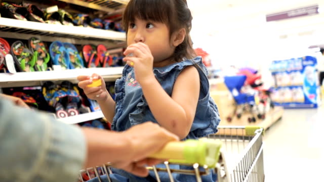 little girl and mother having fun shopping together in supermarket  , slow motion - trolley stock videos and b-roll footage