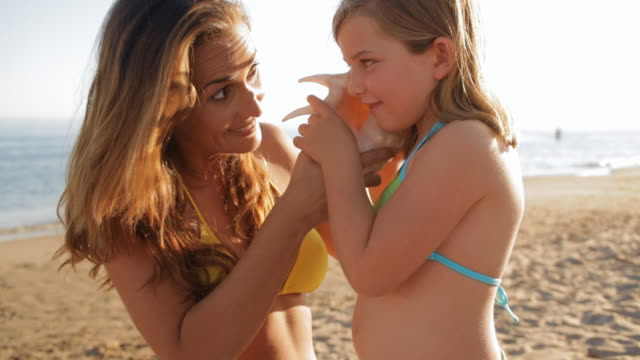 little girl and mother with seashell on beach - seashell stock videos & royalty-free footage