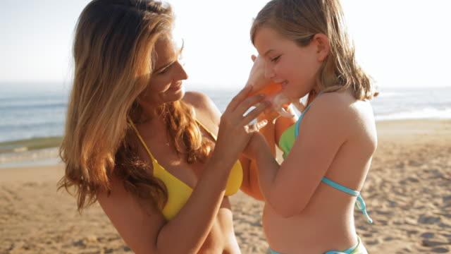 vídeos de stock, filmes e b-roll de little girl and mother with seashell on beach - concha parte do corpo animal
