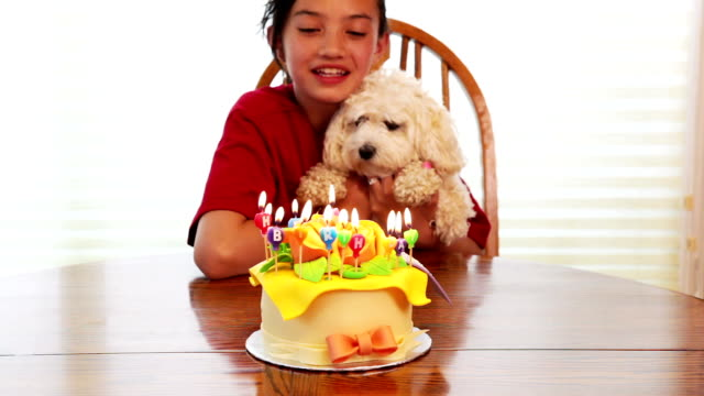 Little girl and pet blowing out birthday candles