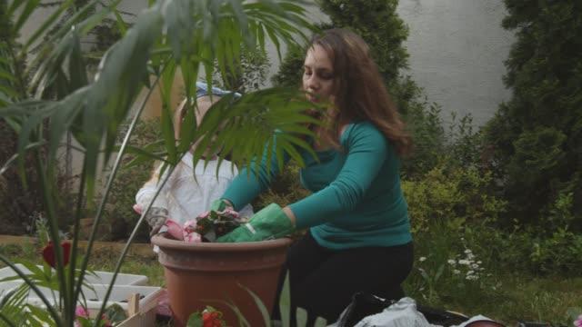 vidéos et rushes de petite fille aidant sa mère dans le jardinage dans leur cour arrière - gant de jardinage
