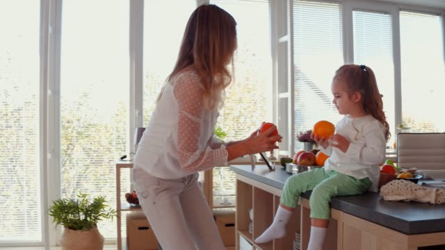 little girl assisting her mother unpack fruit from the groceries bag - domestic kitchen video stock e b–roll