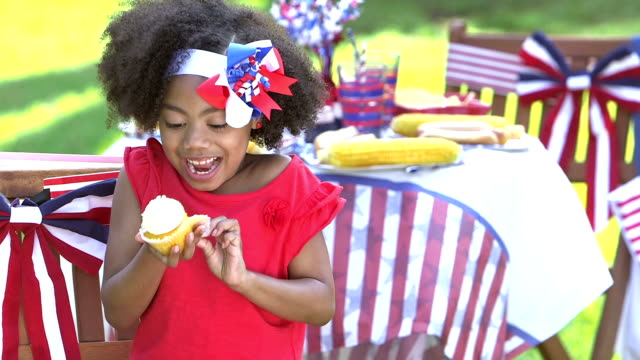 Little girl at July Fourth picnic enjoying cupcake