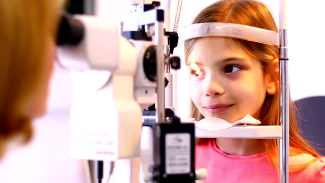 little girl at optician's office. - lens optical instrument stock videos & royalty-free footage