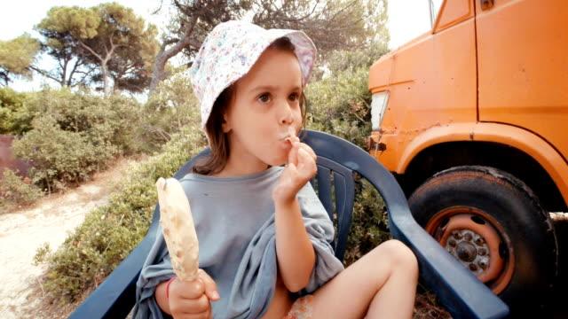 vidéos et rushes de petite fille à la plage, manger des glaces et get malpropre. - ice cream