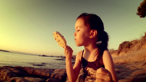 stockvideo's en b-roll-footage met meisje op het strand in de zonsondergang eten ijs en rommelig. - babymeisjes
