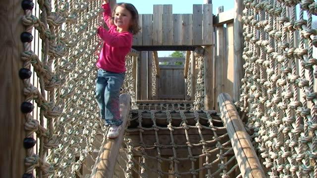 vídeos de stock e filmes b-roll de menina no parque infantil - ponte suspensa