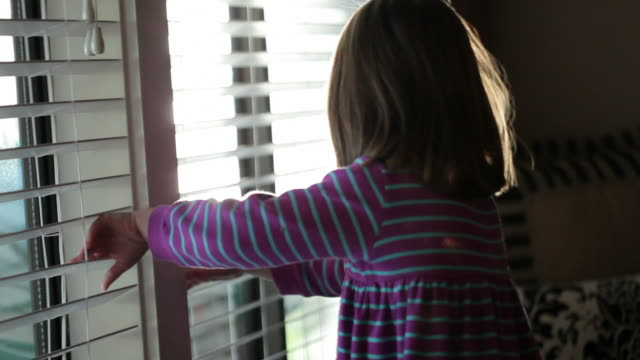 little girl at the window - blinds stock videos & royalty-free footage