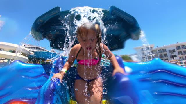 liten flicka på vattenpark promenad under fontän - bak och fram bildbanksvideor och videomaterial från bakom kulisserna