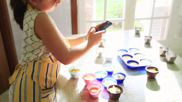 little girl baking at home taking pictures and recording for social media like influencer the muffins she made at home during sunday morning in the kitchen imitating mother role. - one girl only stock videos & royalty-free footage