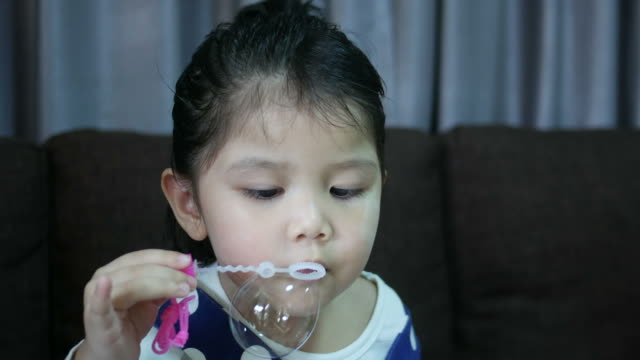 little girl blowing bubble