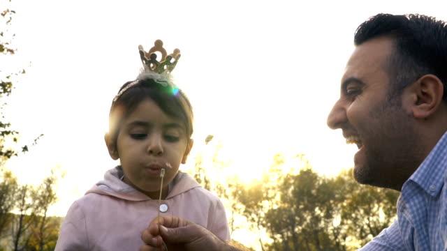 little girl blowing dandelion seeds - dandelion stock videos & royalty-free footage