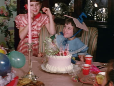 1954 home movie little girl blowing out birthday candles + smiling / sisters kissing her - birthday cake stock videos & royalty-free footage